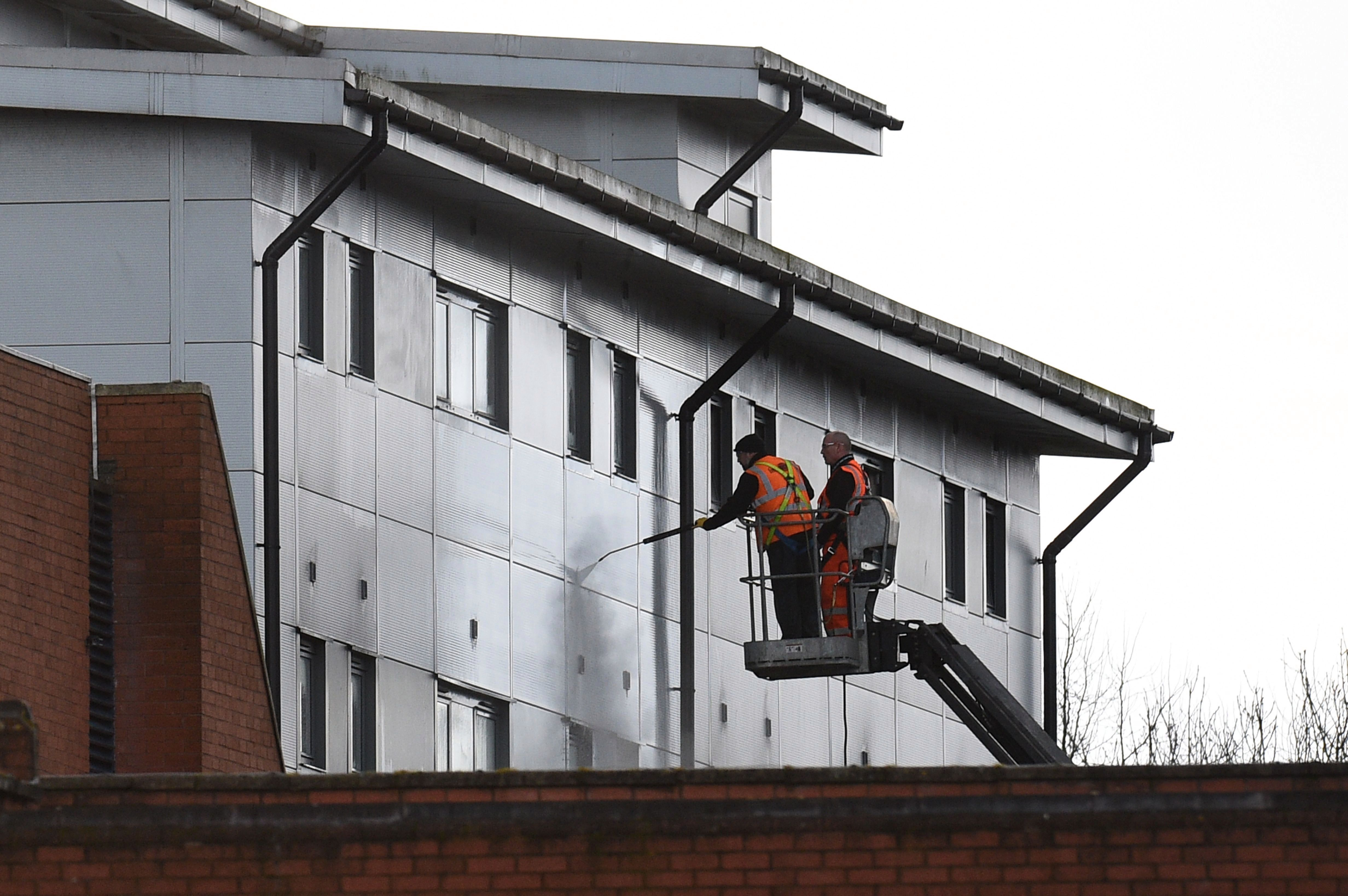 Workers use a pressure cleaner to wash the front of accommodation blocks to house British nationals evacuated from Wuhan