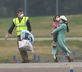 Families wearing face masks were led from the plane by staff at the RAF base