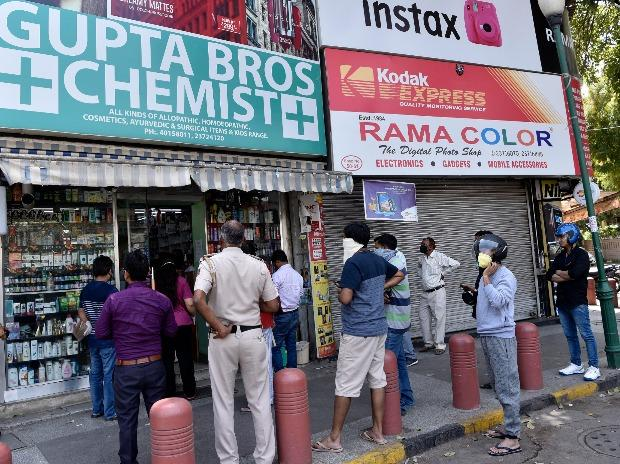 People queue up in front of a pharmacy during a blockade in Delhi and keep a social distance.