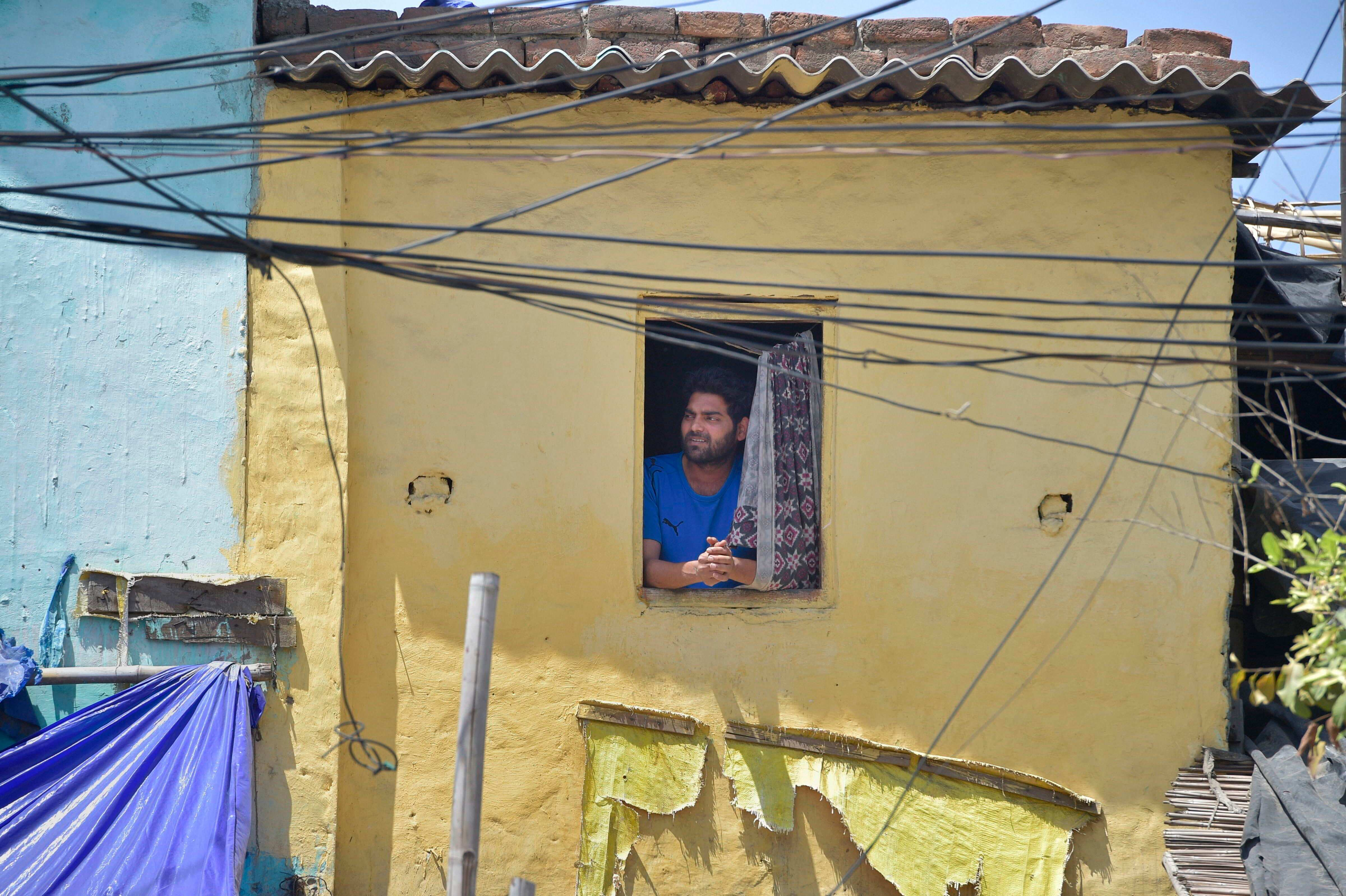 A man looking out the window of his slum during a rural blockade to stop the spread of the coronavirus, in Sek-8 in Neud.