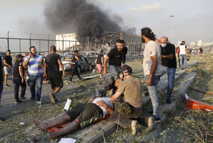 India Tv - Rescue workers help an injured man at the explosion scene that hit the seaport of Beirut, Lebanon, T