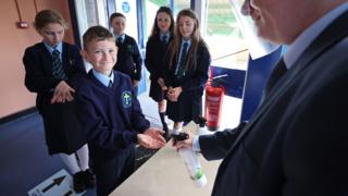 A principal in West Belfast uses sanitiser on pupils hands, as schools in Northern Ireland reopen to pupils following the coronavirus lockdown, 24 August 2020