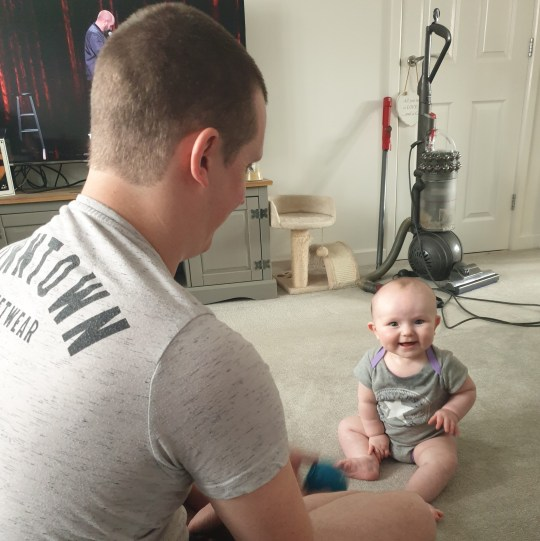 Tom Shirley in his living room with baby Maisie