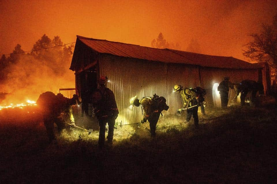 A hand crew clears vegetation from around a barn as the Bear Fire burns through the Berry Creek area of Butte County, Calif., on Wednesday, Sept. 9, 2020.