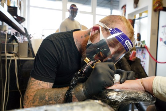 Tattoo artist Anth Matthews, 31, starts a tattoo at the Axe & Anchor tattoo shop in North Shields, North Tyneside as they reopen to customers on following the easing of lockdown restrictions in England. PA Photo. Picture date: Monday July 13, 2020. Nail bars, beauty salons, tattoo and massage studios, physical therapy businesses, spas and piercing services are able to reopen in the latest lifting of restrictions in England. See PA story HEALTH Coronavirus. Photo credit should read: Owen Humphreys/PA Wire