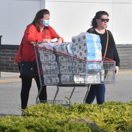 A shopper leaves Costco in Manchester with a shopping trolley full of toilet paper in September 2020
