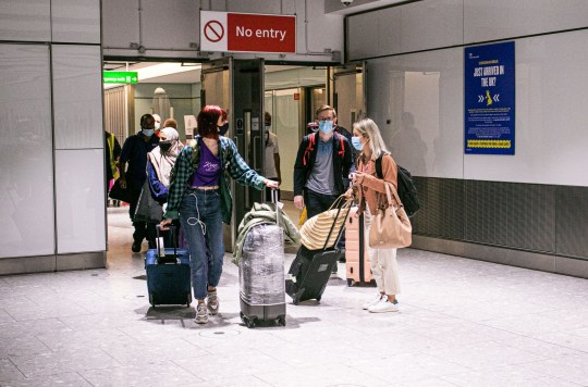 Passengers wearing protective facemasks arriving at Heathrow airport Terminal 5