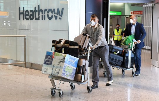 Passengers wearing face masks arrive at Heathrow Airport in London.