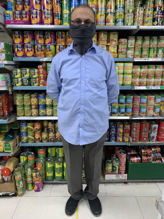 A shop owner wearing a black mask stands in front of a shelf stacked with tins
