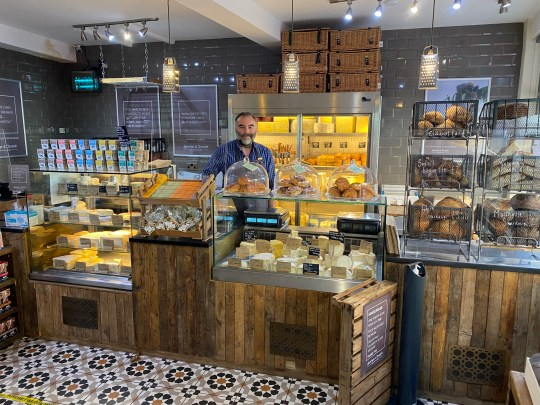 A man with a beard stands behind a wooden counter at a cheesemonger, laden with different types of cheese.