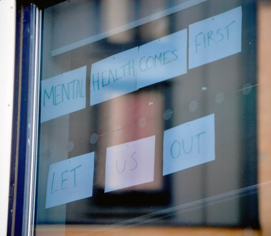 Students leave signs on the windows of their student accommodation that read: 'mental health comes first, let us out'.