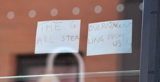 Students leave signs on the windows of their student accommodation that read: 'The government are stealing from us!!'