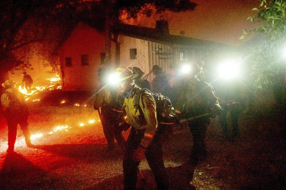A hand crew works to save a home as the Bear Fire burns through the Berry Creek area of Butte County, Calif., on Wednesday, Sept. 9, 2020.