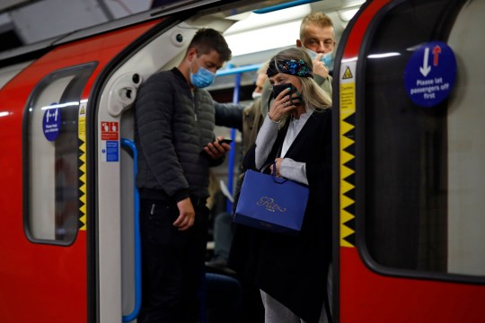 Commuters wearing protective face coverings travel on Victoria line at rush hour in central London