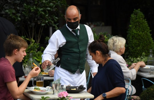 A waiter in a face mask serves in customers in a restaurant.