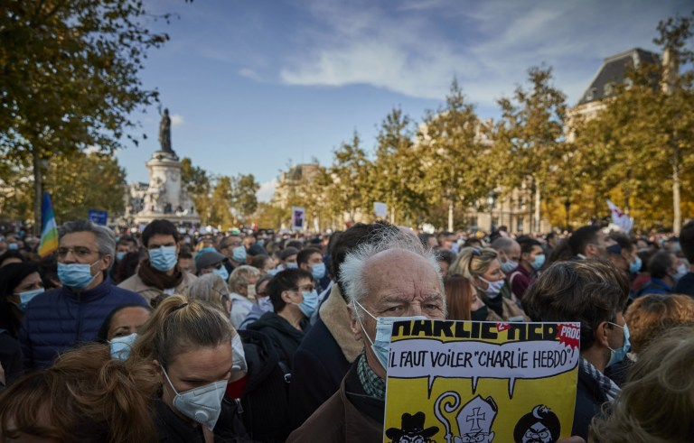 PARIS, FRANCE - OCTOBER 18: A protestor holds a copy of the satirical newspaper Charlie Hebdo during an anti-terrorism vigil at Place de La Republique for the murdered school teacher Samuel Paty who was killed in a terrorist attack in the suburbs of Paris on October 18, 2020 in Paris, France. Thousands of people turned out to show solidarity and express their support for freedom of speech in the wake of Friday's attack. France launched an anti-terrorism investigation after the October 16 incident where police shot the 18 year-old assailant who decapitated the history-geography teacher for having shown a caricature of prophet Mohamed as an example of freedom of speech at the College Bois d'Aulne middle-school. (Photo by Kiran Ridley/Getty Images)