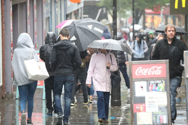 People walk through rain in Nottingham city centre