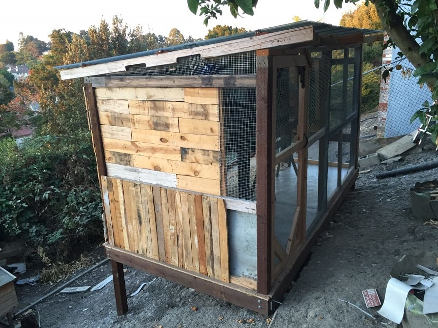 a large chicken coop made of pallets and recycled wood