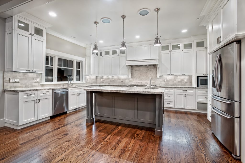 Elegant hanging lamps in this adapted kitchen with centre island