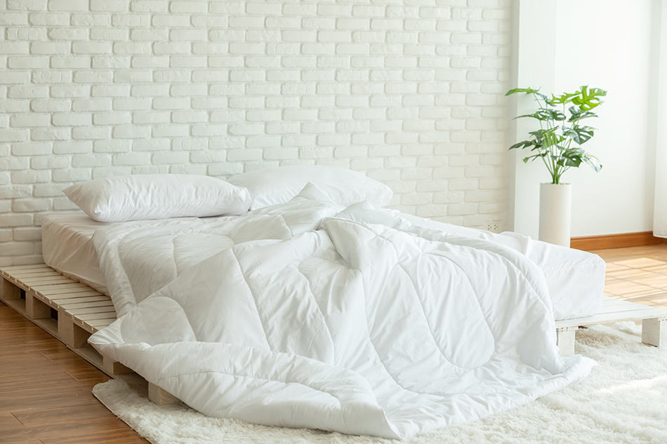How do you prevent yellow sweat stains on bed sheets?