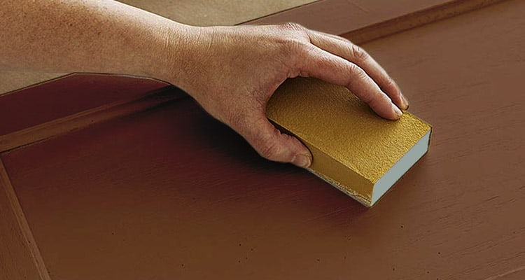 Scrubbing furniture with sandpaper