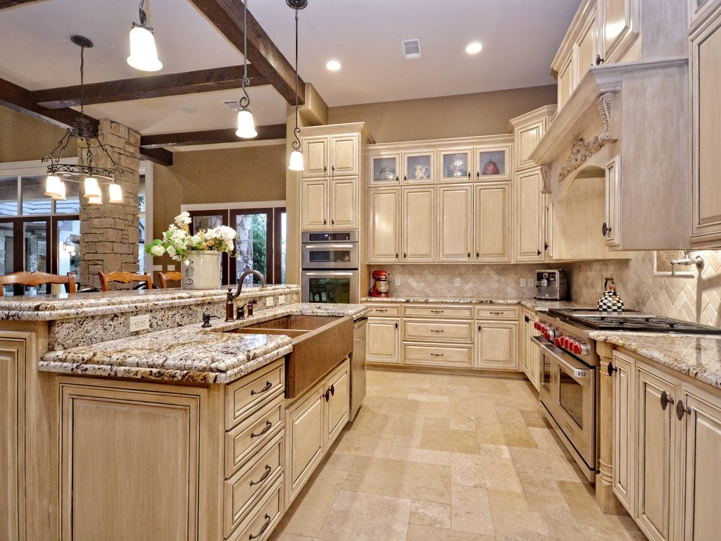 Traditional kitchen with limestone tiled floor and flat-panel cabinets