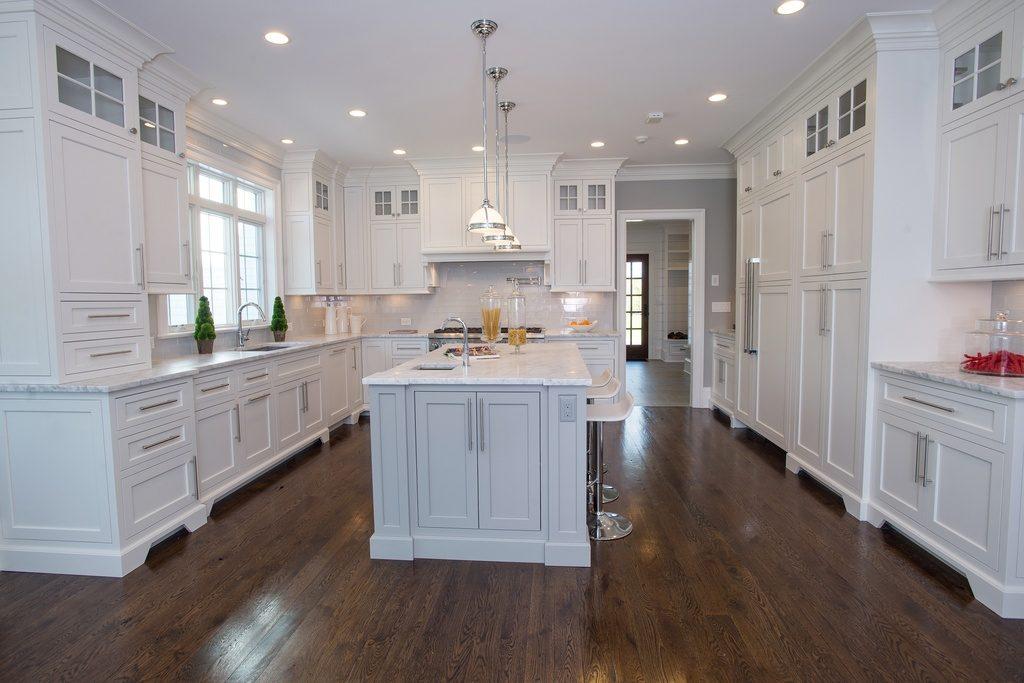 Traditional white kitchen cabinets with Silestone quartz worktops and dark oak floors.