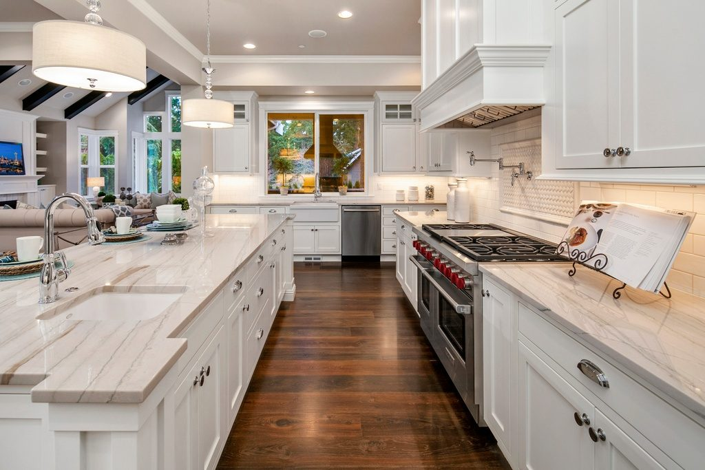 White kitchen with marble counters, subway tiles, hickory wooden floors.