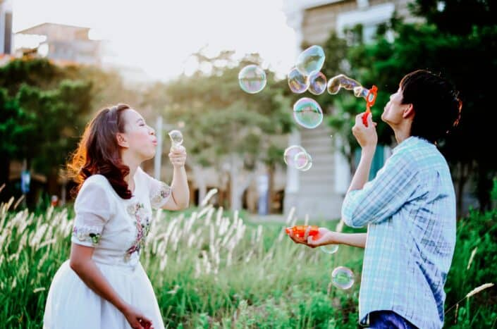 a man and a woman blowing bubbles in the street...