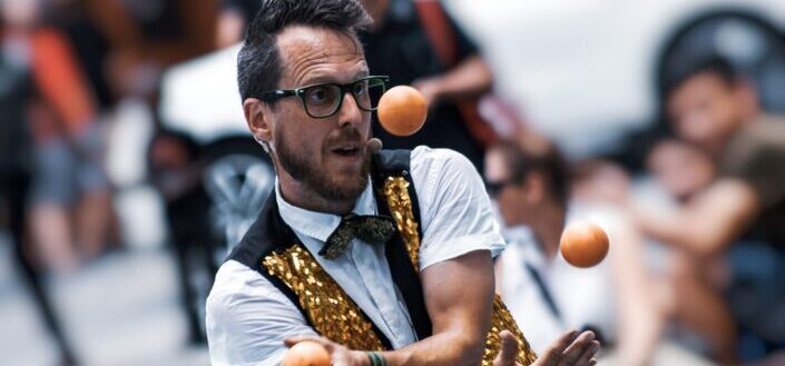 a man in glasses juggling three bullets at once.