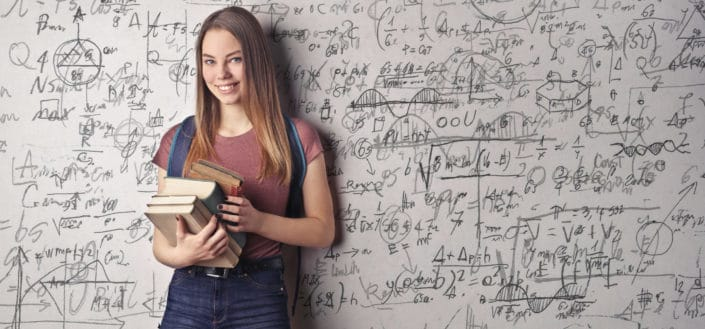 A woman smiles and holds books with a bunch of mathematical formulas in the background.
