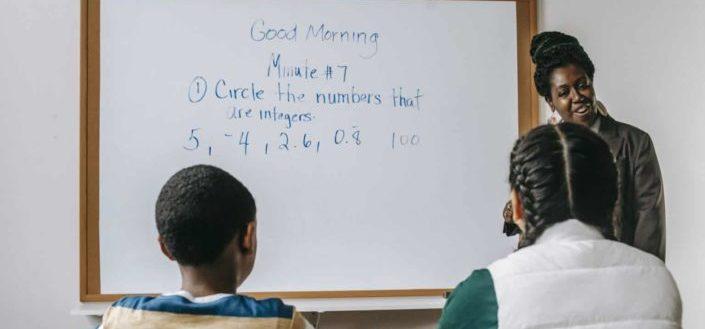a woman teaches math to two kids