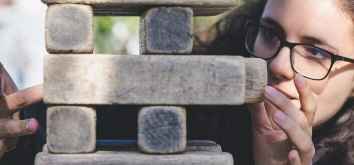 A woman with glasses is trying to get a block of Jenga out of a Jenga tower.
