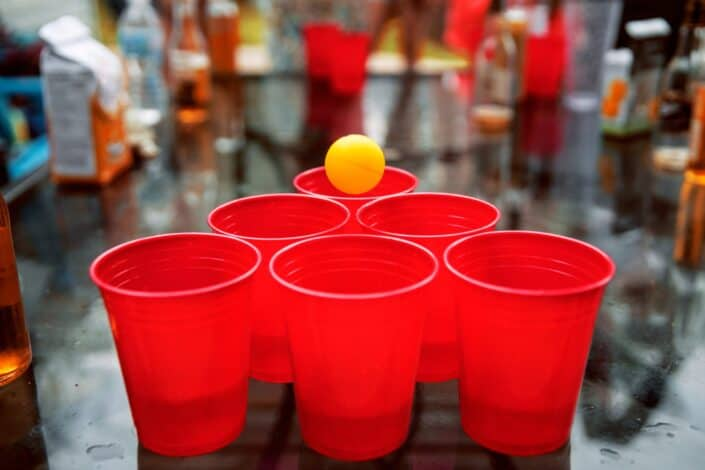 Six red cups in a triangle with an orange ping pong ball to place in one of the cups.