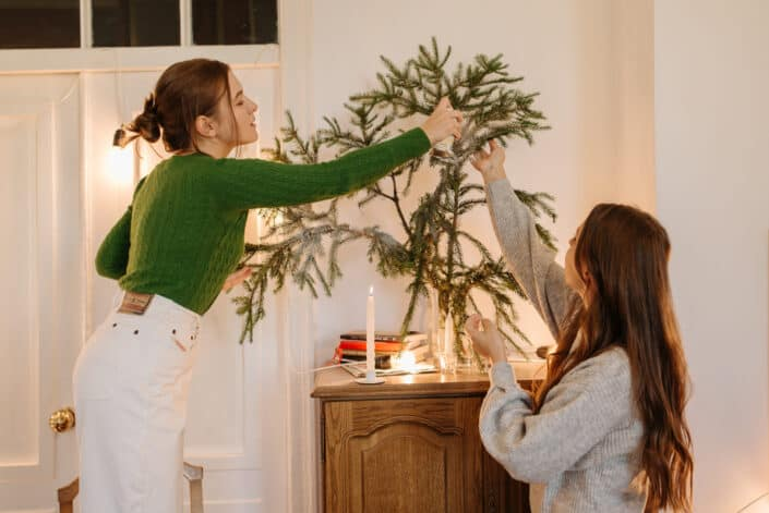 two women planting a tree in a house