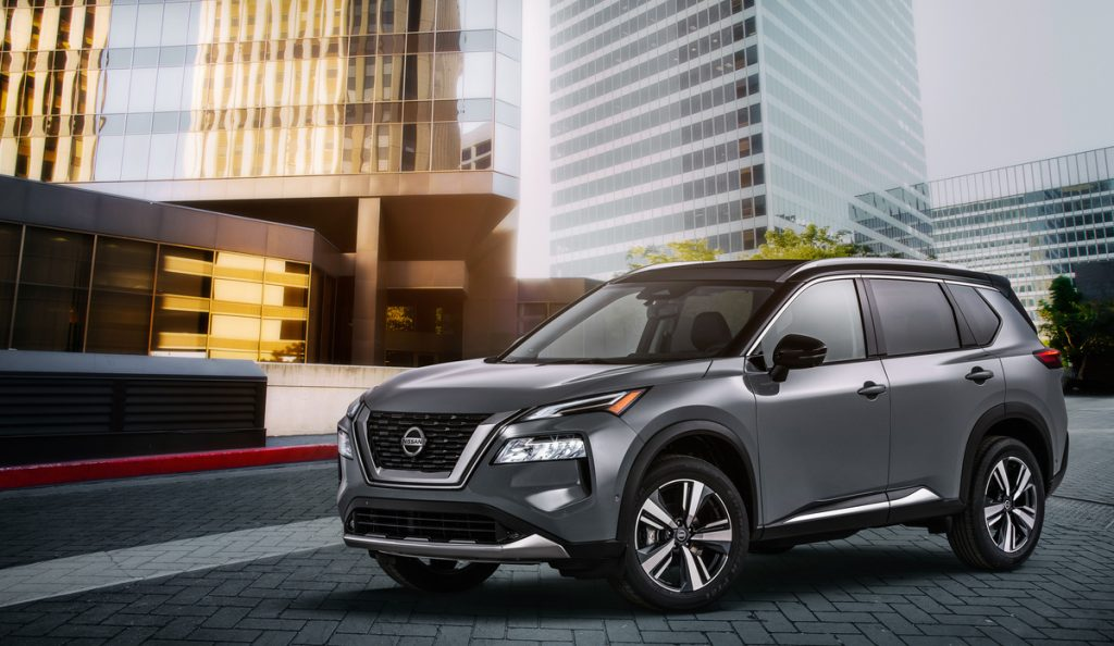 A side view of a gray 2021 Nissan Rogue Platinum AWD sitting parked in front of a building