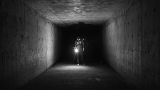 Flashlight in an underground concrete bunker.