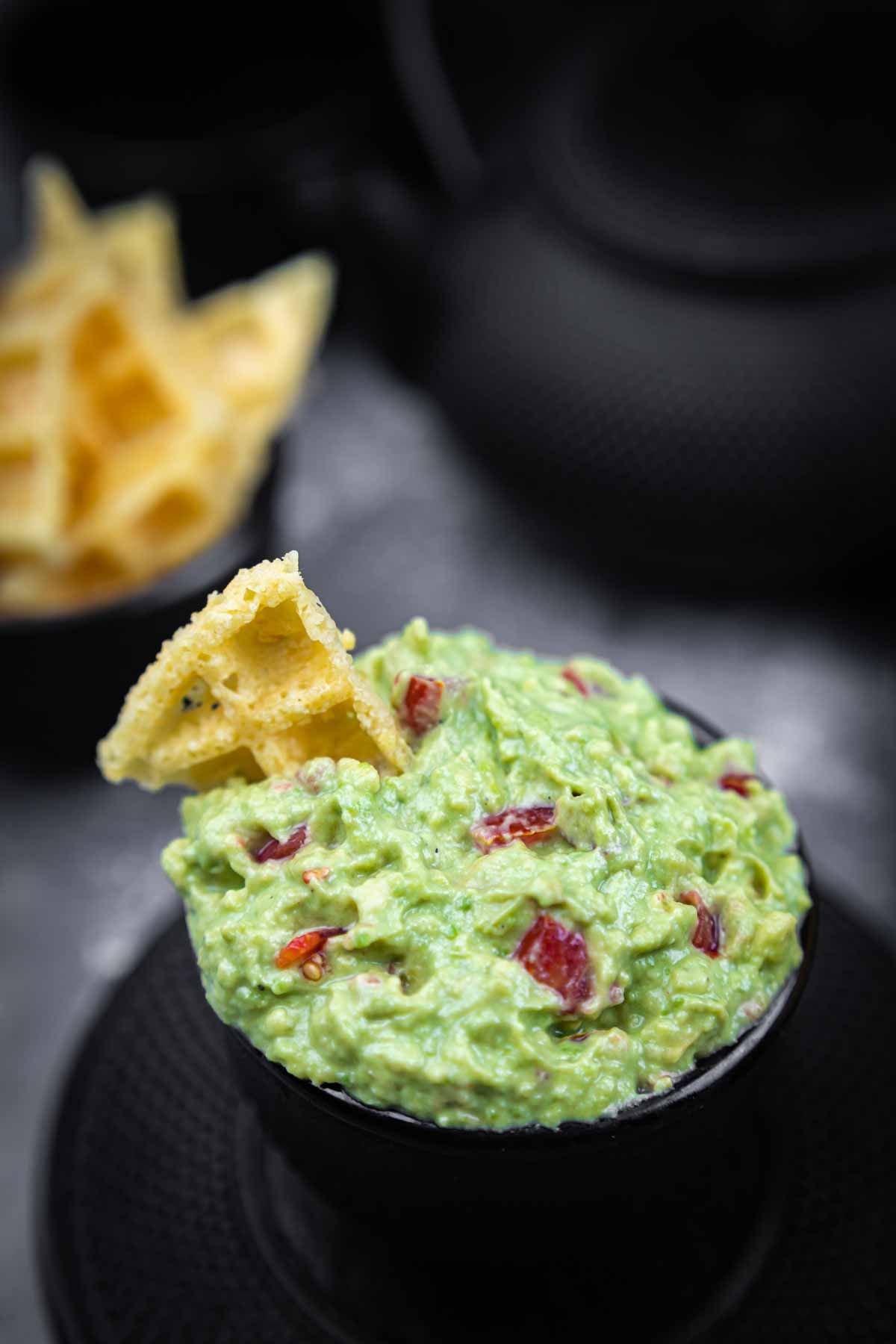 Super Simple Keto Guacamole in a black bowl with a chip dipped