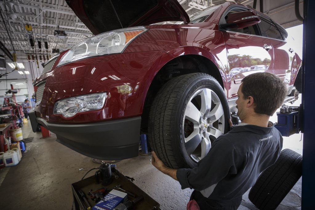 Technician Dave Serdar rotates the tires on a Chevy Traverse
